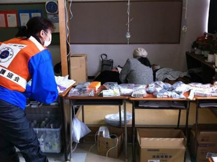 東日本大震災から8日目、兵庫県医師会と兵庫県看護協会からなるJMAT(日本医師会災害医療チーム)は、石巻の中学校に診療所を開設させていただきました。写真は私ですが、処方されたお薬を詰め、患者さんに説明しようとしているところです。避難所開設した日に100人の避難者さんが診療に来てトイレに行く暇もないくらい大忙しでした。